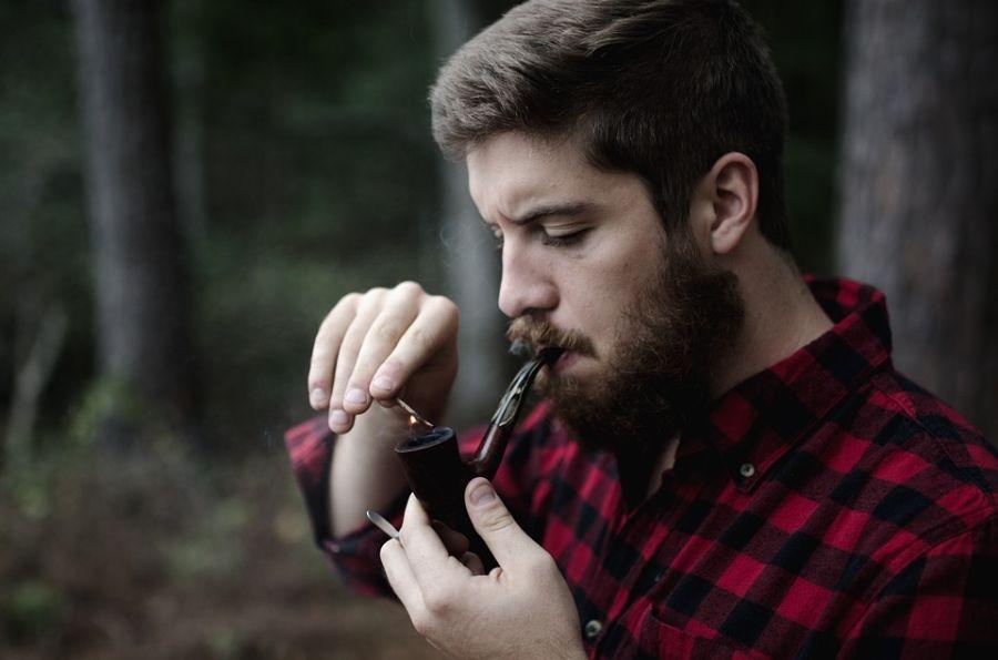brodaty mężczyzna rozpala fajkę z tytoniem