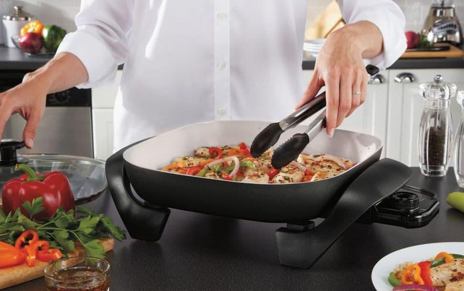 kobieta gotuje mięso z warzywami na elektrycznej patelni