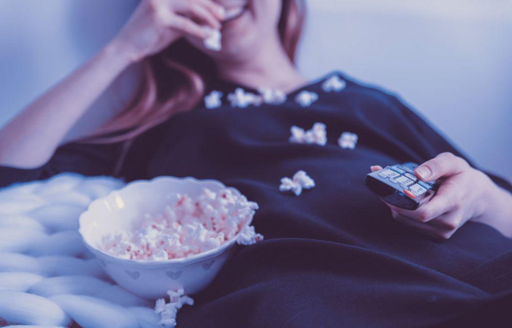 Kobieta jedząca popcorn przed telewizorem