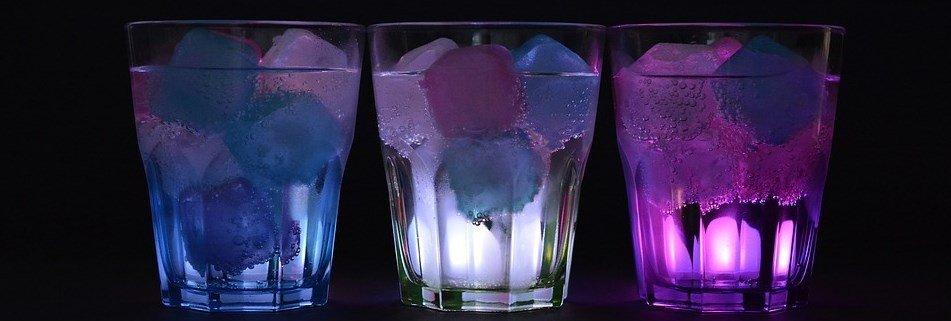 trzy drinki w różnych kolorach z kostkami lodu