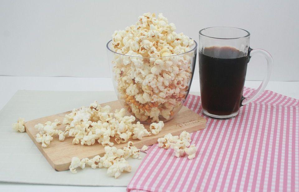 Miska z popcornem, a obok szklanka z colą