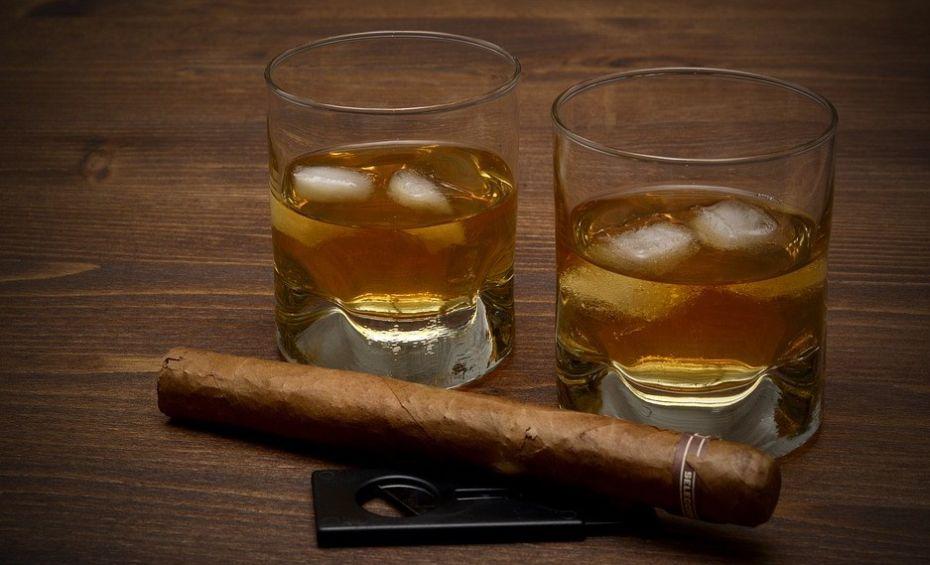 dwie szklanki whiskey z lodem, a obok cygaro