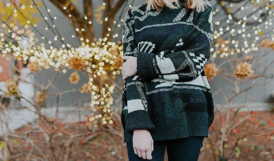 młoda blondynka w długim swetrze we wzory