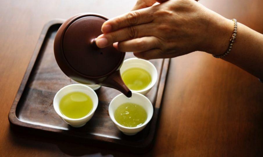 nalewanie żółtej herbaty do trzech filiżanek