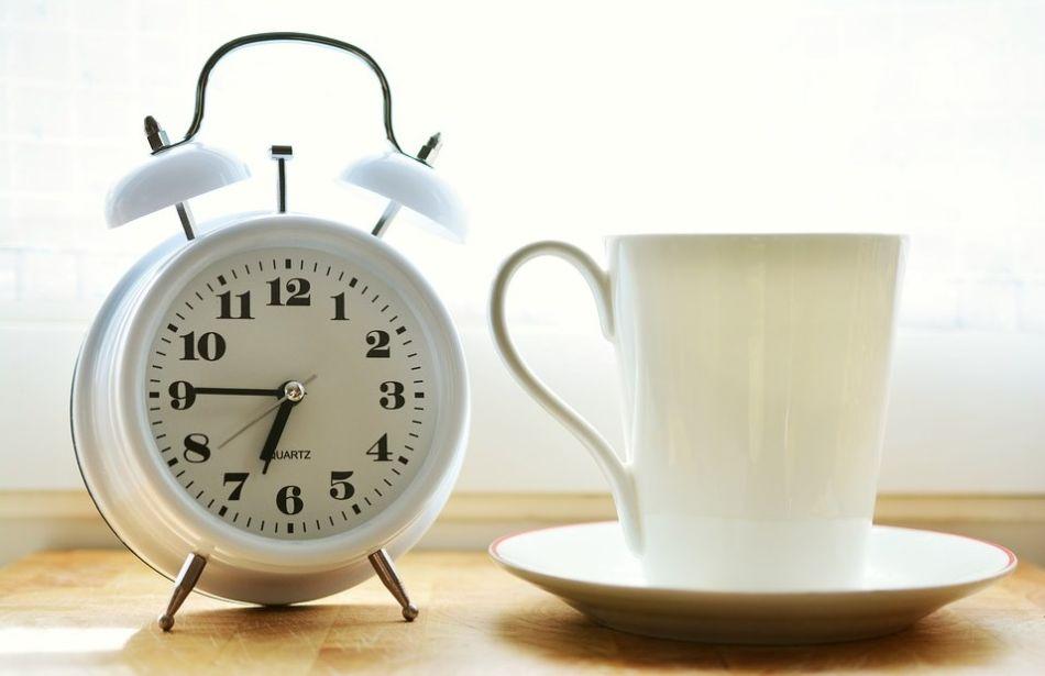 klasyczny budzik obok filiżanki kawy