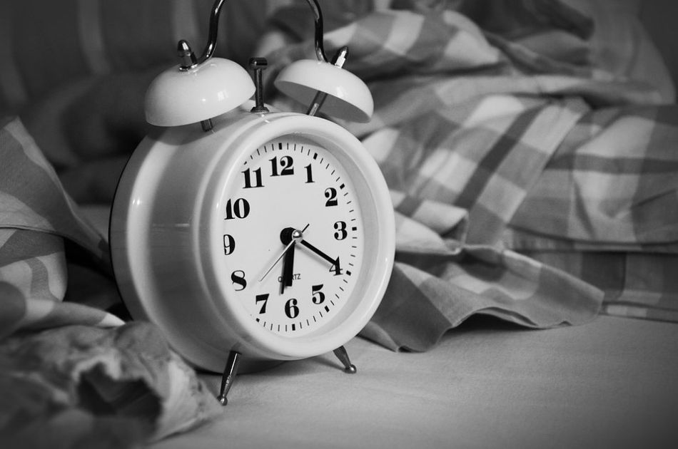 klasyczny budzik położony na łóżku