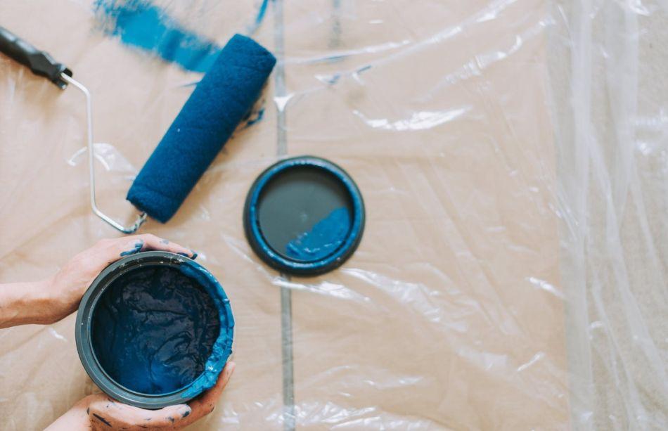 folia malarska, a na niej wałek w niebieskiej farbie