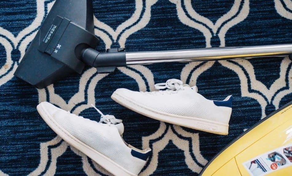 wzorzasty dywan, a na nim odkurzacz i buty