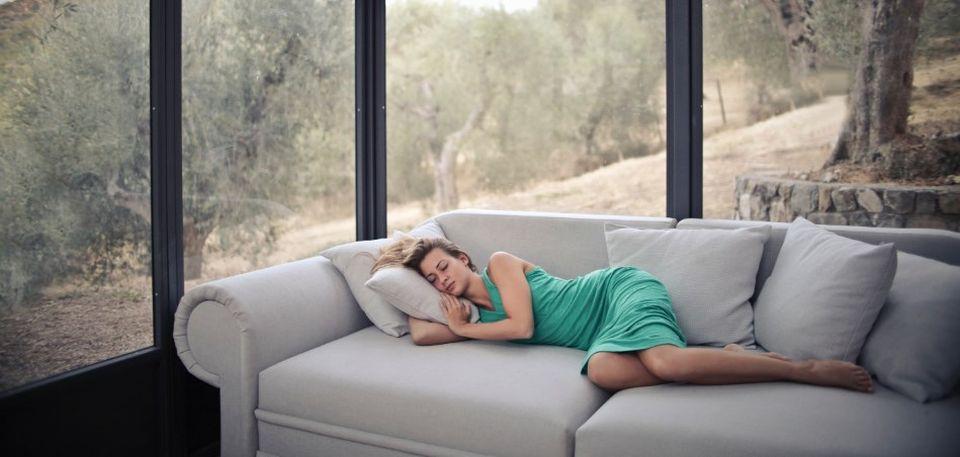 kobieta, która śpi na wielkiej kanapie w wielkim domu
