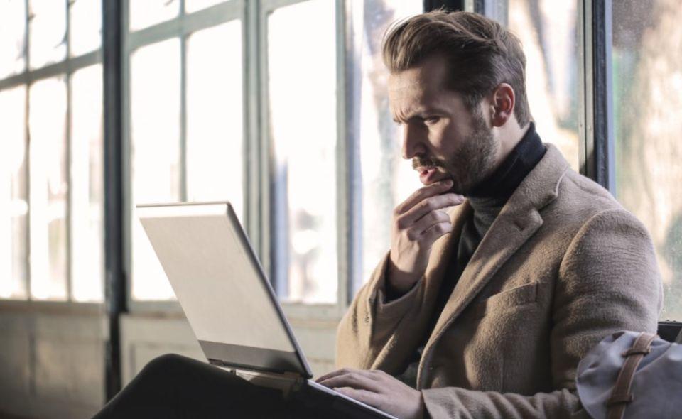 elegancko ubrany brodacz przed laptopem