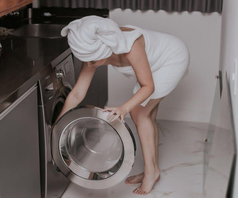 kobieta obsługująca pralkę w domowej pralni