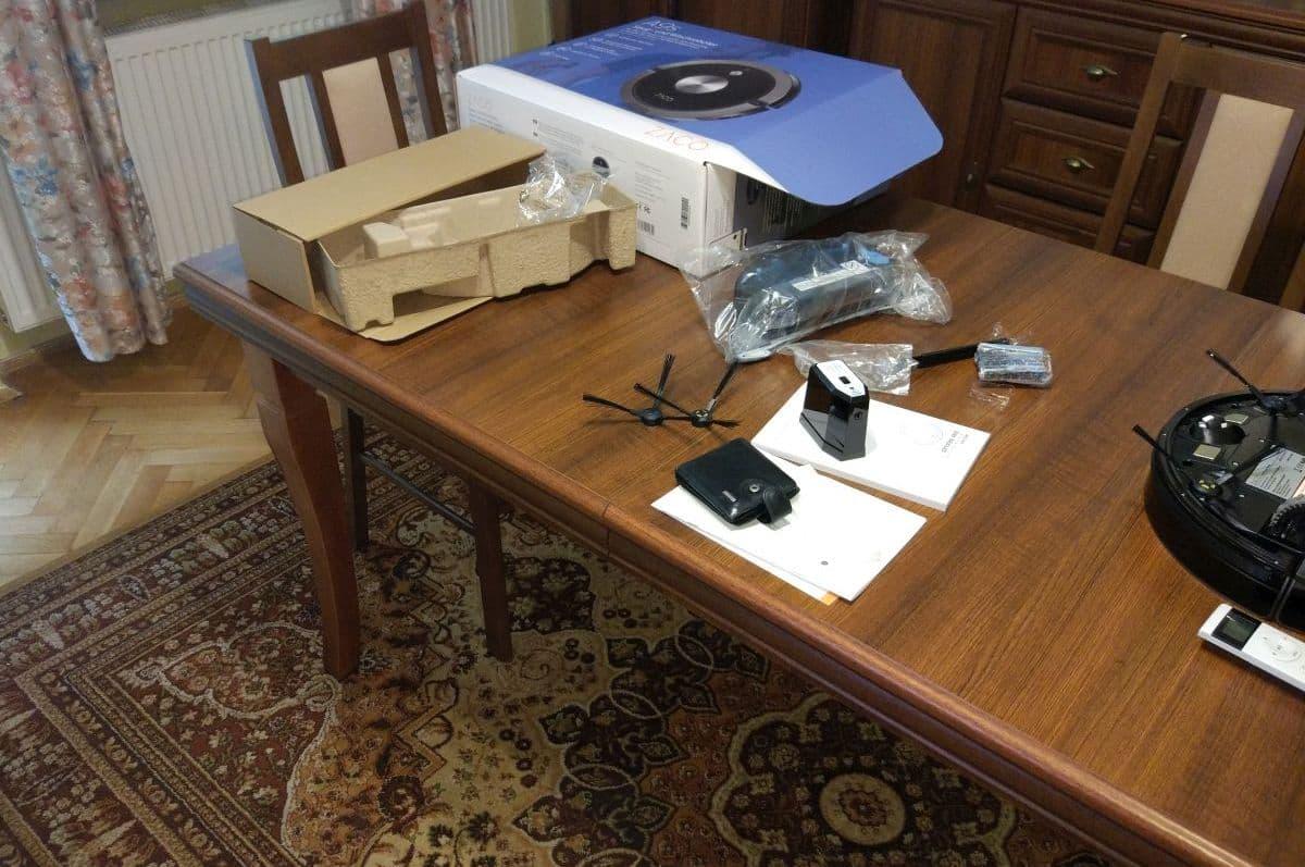 robot odkurzał dywan wokół stołu i krzeseł