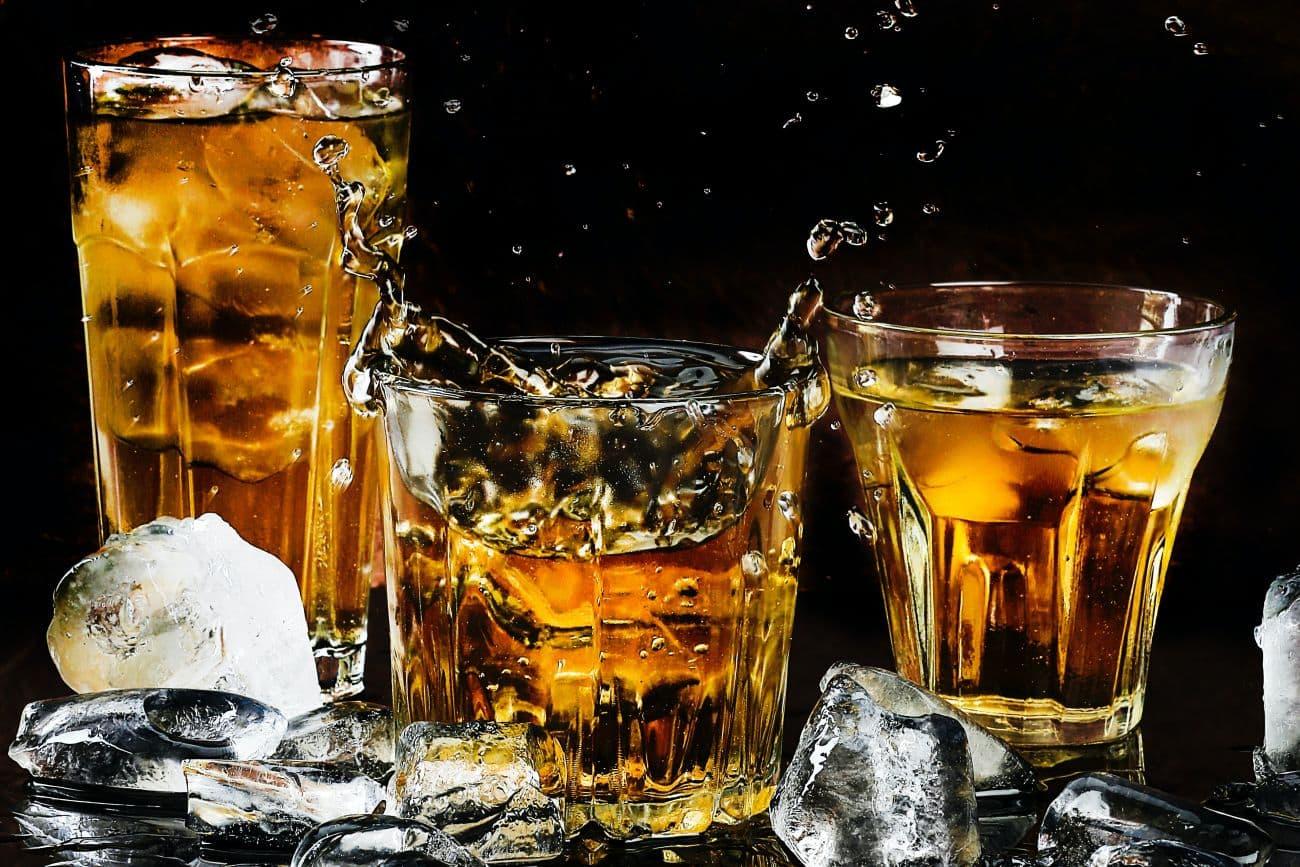 kostki lodu z kostkarki wrzucone do szklanek z napojami i trunkami