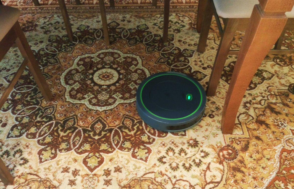 Moneual MBOT 500 odkurza dywan pod stołem