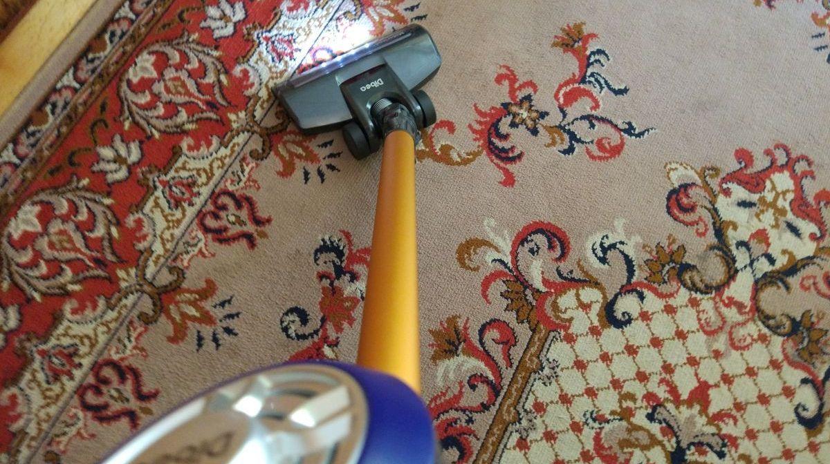 Odkurzacz pionowy Dibea V008 Pro podczas rutynowego odkurzania dywanu