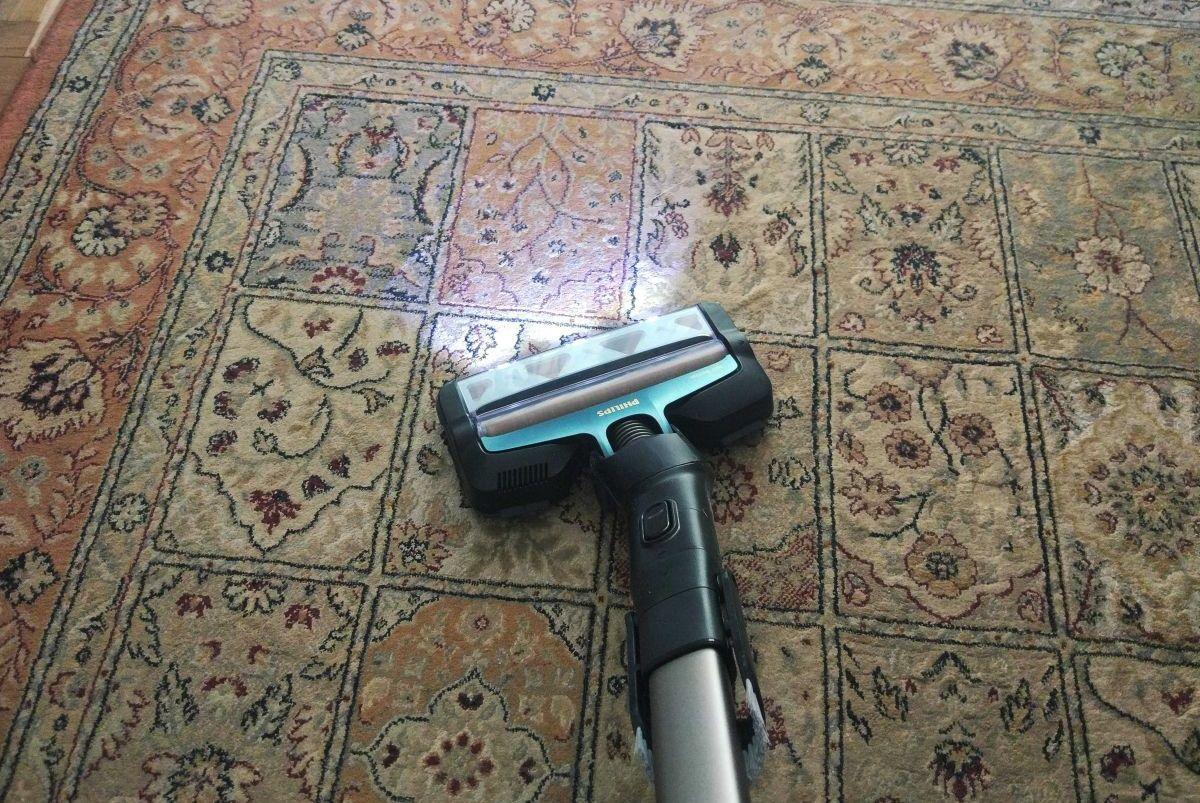 Odkurzacz pionowy Philips XC8149/01 podczas odkurzania dywanu pełnego kociej sierści