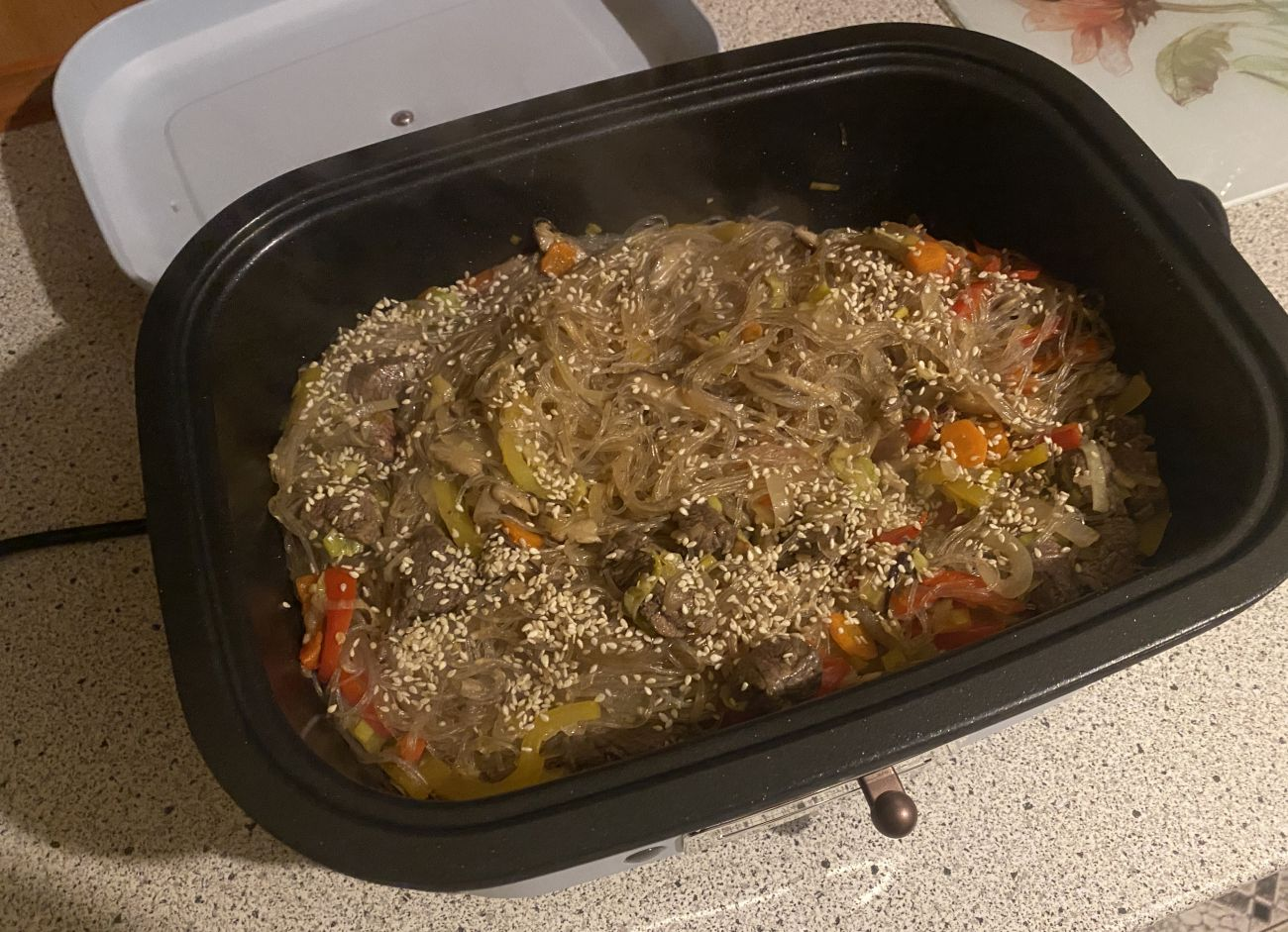 Kuvings MultiGrill podczas testu gotowania makaronu z wołowiną i warzywami - ostatni etap z sezamem