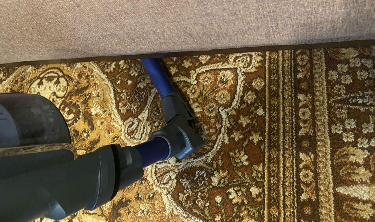 Wjeżdżanie zgiętą rurą Flex odkurzacza Tefal X-Force Flex 11.60 Aqua TY9890 pod sofę